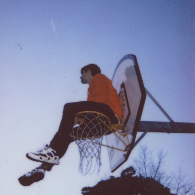 Der Künster Hauskey sitzt auf einem Basketballkorb. Man sieht ihn von unten, der Himmel ist dunkelblau wie kurz nach dem Sonnenuntergang.