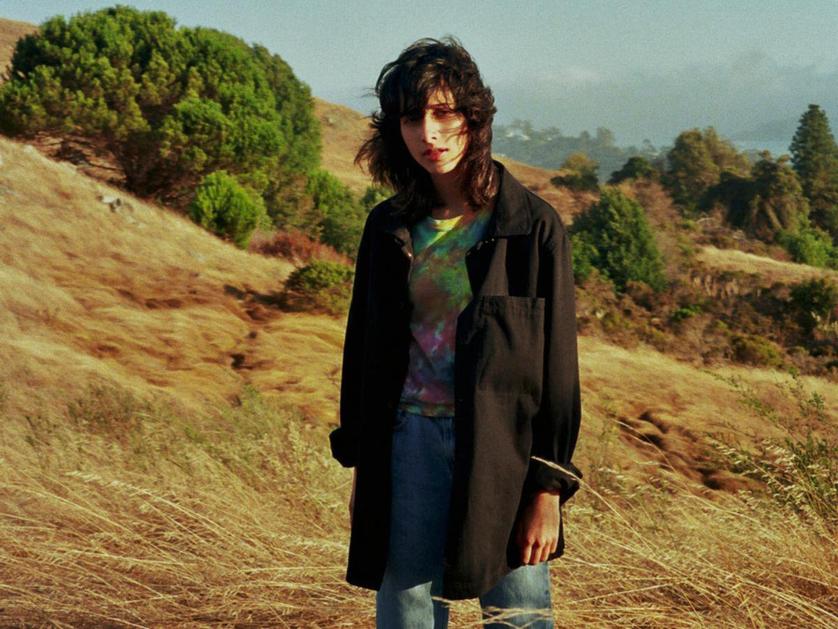 Sängerin Kali steht auf einem Feld mit Wind der ihr durch die Haare weht