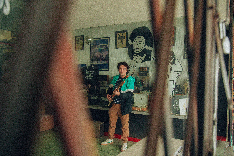 Lou Beauty plays guitar in his studio