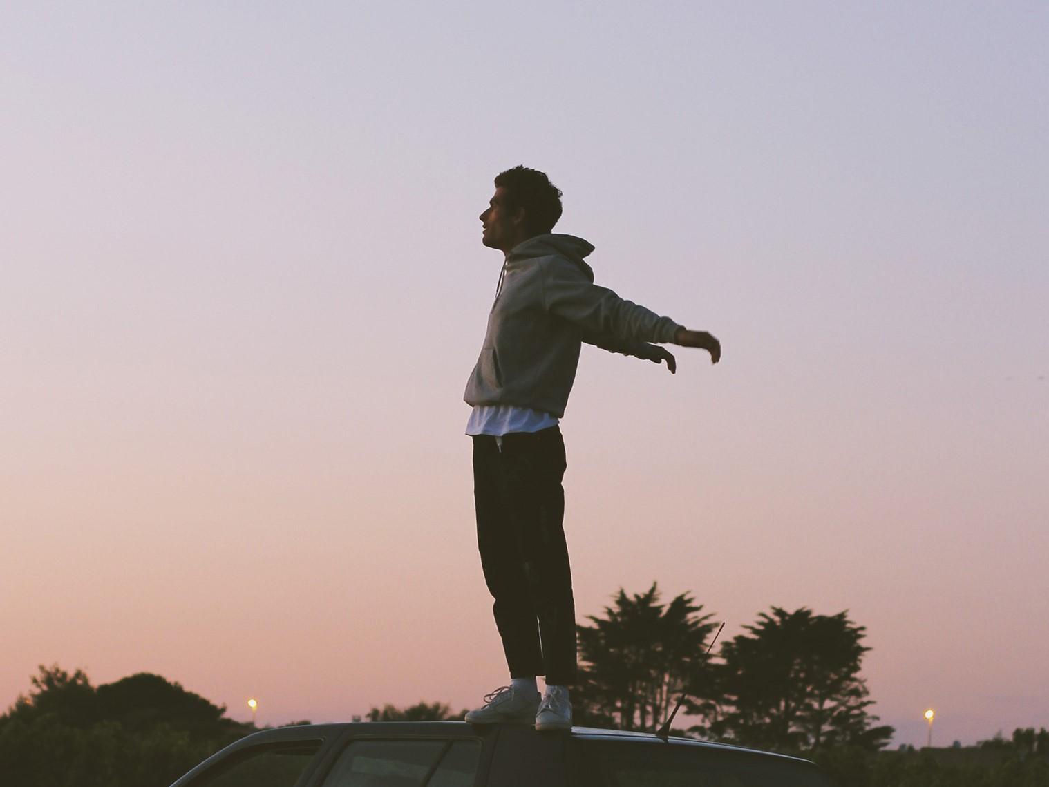 Oscar Anton steht auf einem Auto mit Sonnenaufgang im Hintergrund